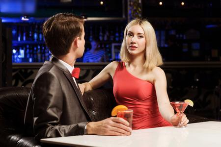 vergezeld: Jonge knappe man in een bar begeleid door elegante dame
