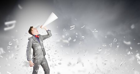 speaking trumpet: Young businessman screaming emotionally in paper trumpet