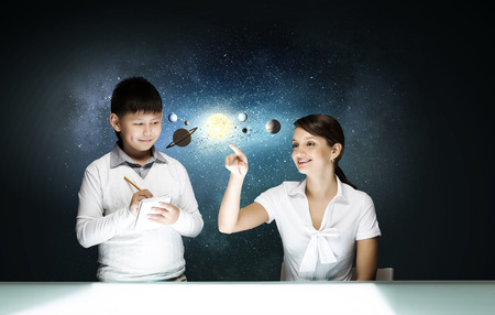 pupils: Teacher and two pupils at astronomy lesson exploring space