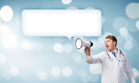 young male doctor: Young male doctor screaming in megaphone emotionally Stock Photo