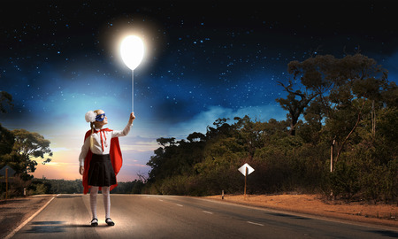 Cute girl of school age in superhero costume with balloon in hand Stock Photo