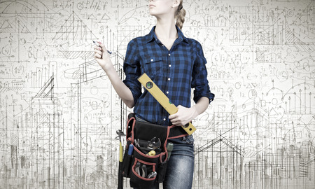 Close up of woman mechanic with ruler in hand against city background photo
