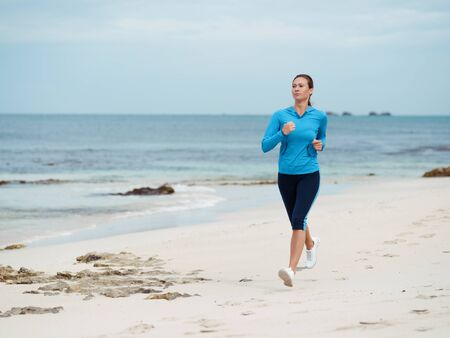 activewear: Sporty young woman running on the sea coast