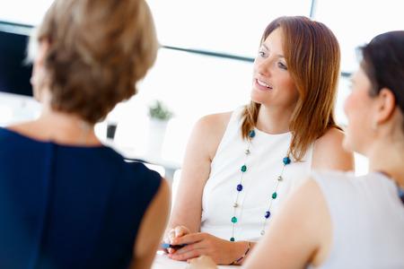 women talking: Attractive businesswoman talk in office