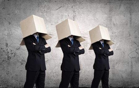 hidden success: Unrecognizable business people wearing carton boxes on head