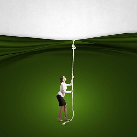 commercialism: Young businesswoman pulling curtain with rope. Place for text Stock Photo