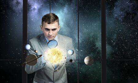 Young businessman examining planets of space spinning around photo