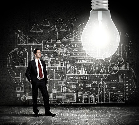 Businessman and light bulb with business sketches at background photo