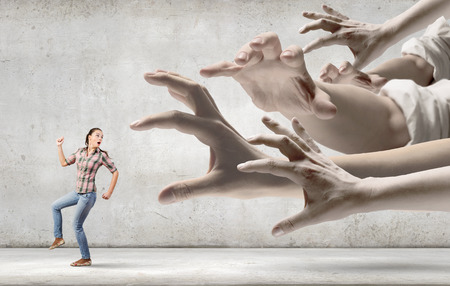 scared woman: Young woman in casual running away from big hand