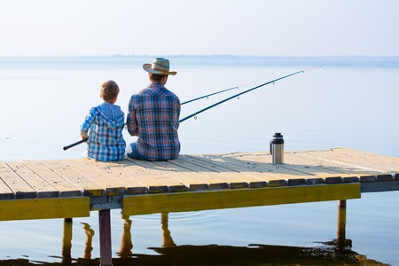 boy and his father fishing together from a pier Stock Photo