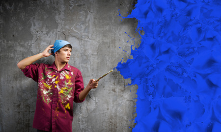 redecorating: Young handsome man painter with brush in hand Stock Photo