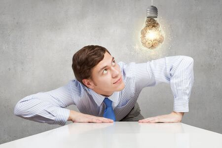 structuring: Businessman leaning on table and looking at bulb with gears