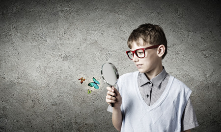 School boy examining butterfly with magnifying glass photo