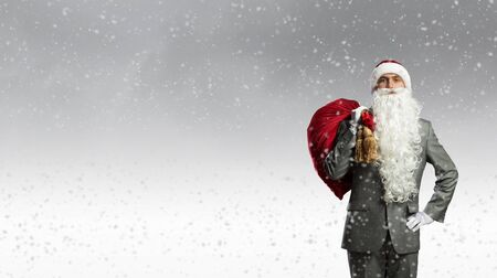 gift behind back: Businessman in Santa hat with red gift bag behind back Stock Photo