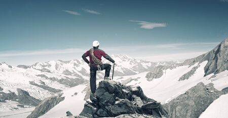 Mountaineer at peak of mountain enjoying natural landscape photo