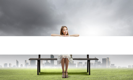 Young asian woman sitting on bench with blank banner photo