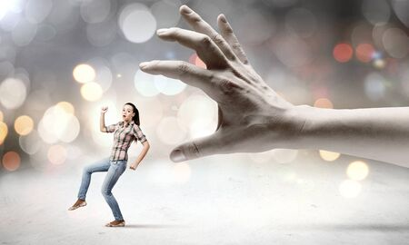 escaping: Young woman in casual escaping from big male hand Stock Photo