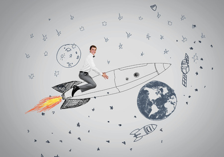 Young businessman flying in sky on drawn rocket photo