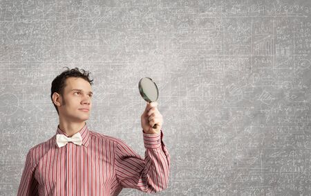 Young funny science man looking in magnifier photo