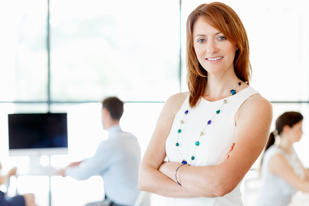 collegue: Young businesswoman standing in office with her collegue on the background