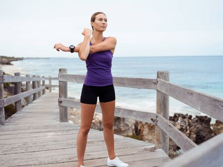 activewear: Sporty young woman stretching on the sea coast Stock Photo