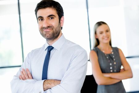 collegue: Young businessman standing in office with his collegue on the background Stock Photo