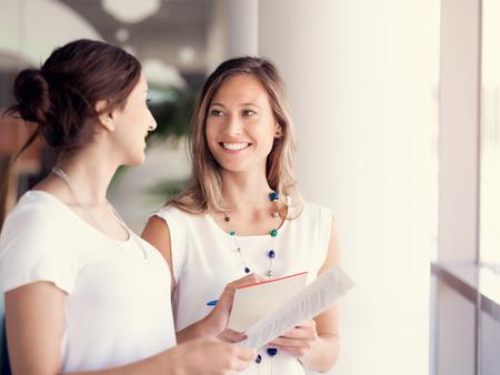 reunion de trabajo: Dos colegas mujeres de pie junto a la otra en una oficina