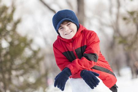Little cute boy having fun in winter park photo