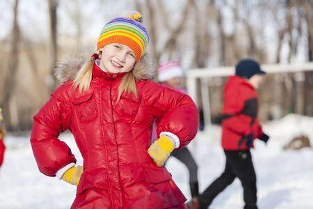 Cute girl of school age having fun in winter park photo