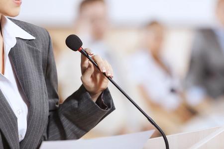 hablar en publico: Empresaria de pie en el escenario y la presentaci�n de informes para la audiencia Foto de archivo