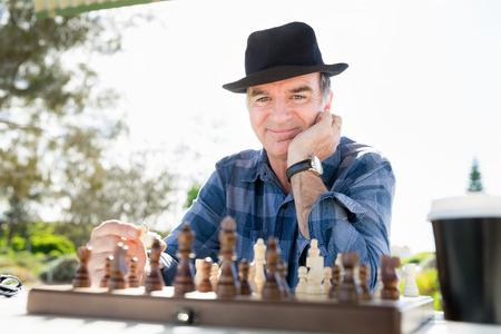 Oudere man buiten zitten met schaken Stockfoto