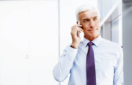 Businessman talking over phone in office photo