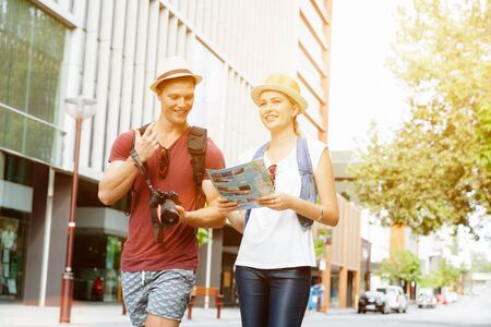 Happy young couple as tourists with a map photo