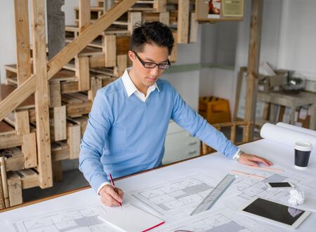 Young chineese engineer working in office photo
