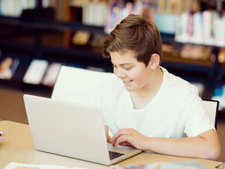 Teenage boy sitting with tablet in library photo
