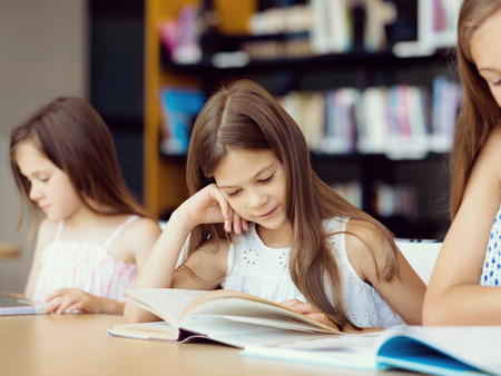 young schoolgirl: Little girls reading books in library Stock Photo