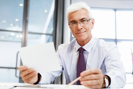 businessman pondering documents: Businessman in office working with papers