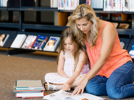 intelligently: Little girls with their mother reading books in library