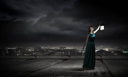 darkness: Young woman with lantern walking in darkness