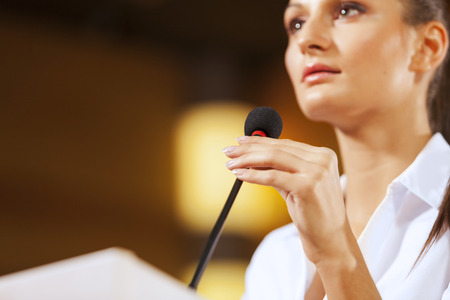 Businesswoman standing on stage and reporting for audience Фото со стока