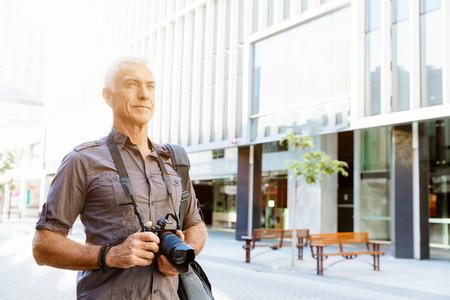 Senior man with camera in city photo