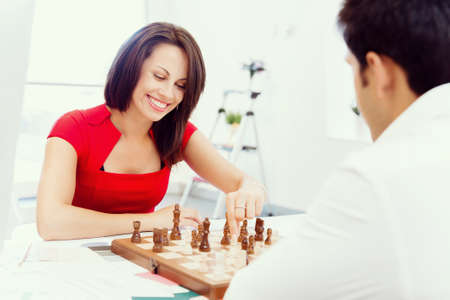 robustness: Businesswoman playing chess in office