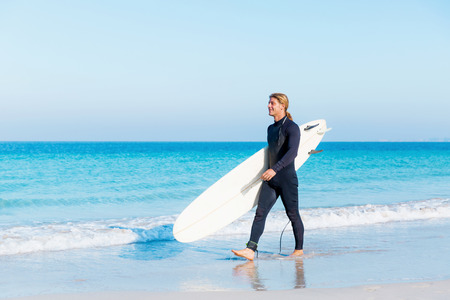 male surfer: A young surfer with his board on the beach