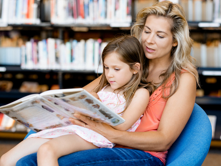library: Little girls with their mother reading books in library