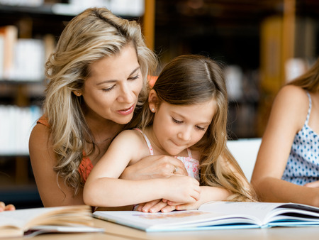 young people: Little girls with their mother reading books in library