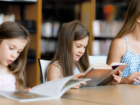 intelligently: Little girls reading books in library Stock Photo