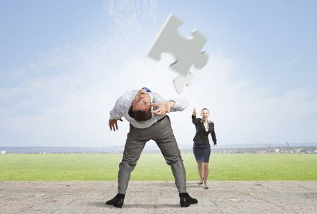 bent: Businessman bent over and evading from flying puzzle element