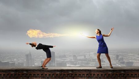 agression: Young businesswoman benting back to evade from fire Stock Photo