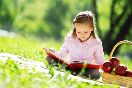 Child with book having picnic in summer park photo