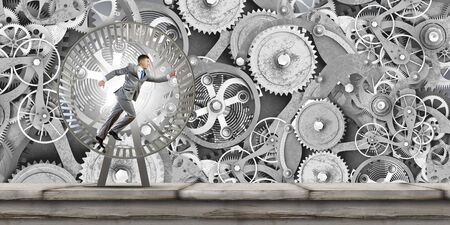 Young businessman running in wheel of gears mechanism photo